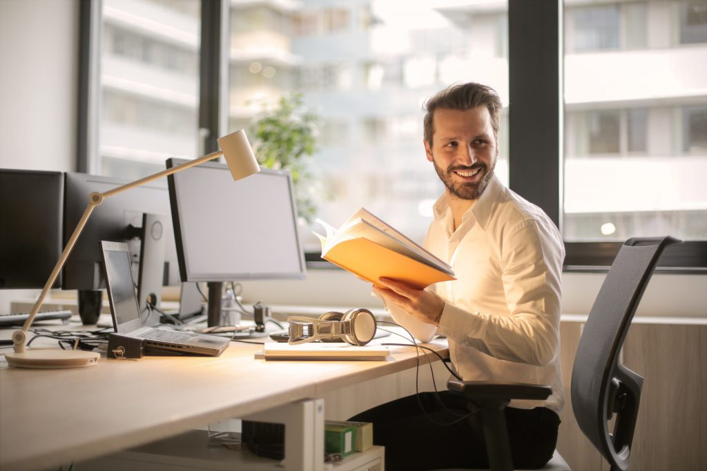 smiling man with book at desk wearing white shirt